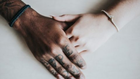 Black and white hands embrace