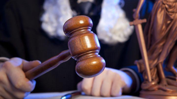 Judge wearing wig using gavel