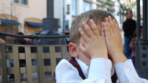 Child covering his face