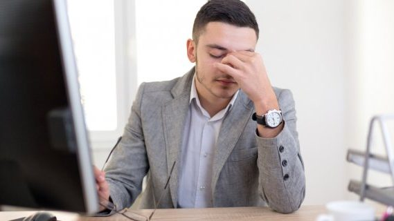 Male employee stressed at work