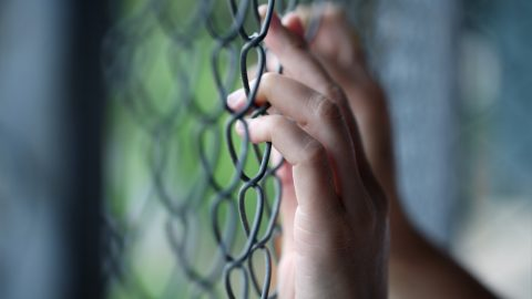 Hand holding onto detention fence