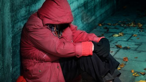 Homeless person wearing red jacket
