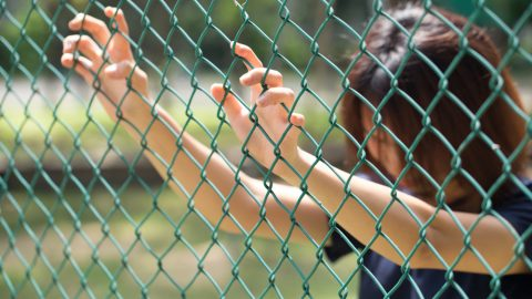 Woman holding onto prison fence