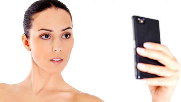 Woman taking naked selfie