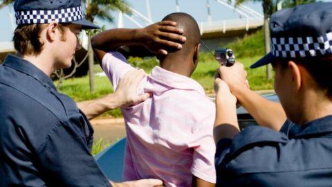 Police pointing gun at motorist