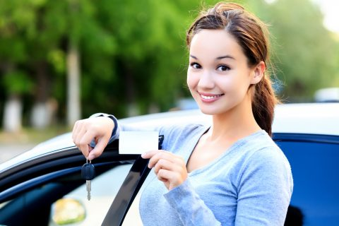 Young woman driver smiling with car licence and key