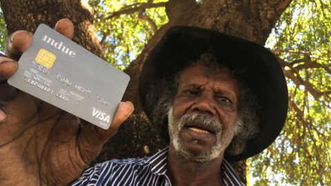 Man displaying a cashless debit card
