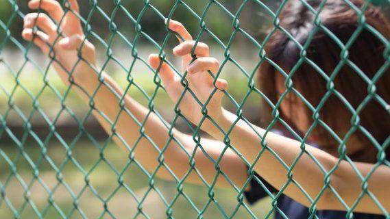 Woman prisoner at fence