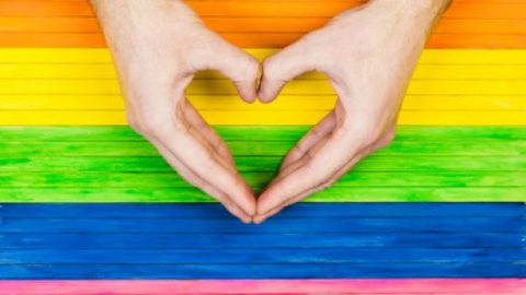 Gay flag and hands forming a heart