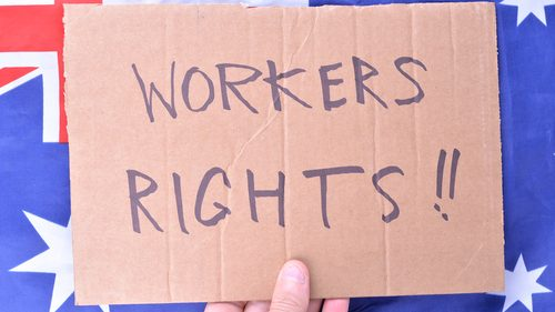 Worker Rights sign in front of an Australian flag